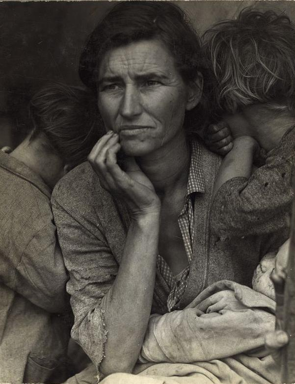 A mother, holding her two children, rests her chin in her hand and looks off