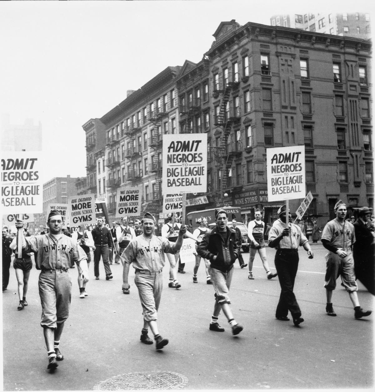 Protesters march in the streets holding signs