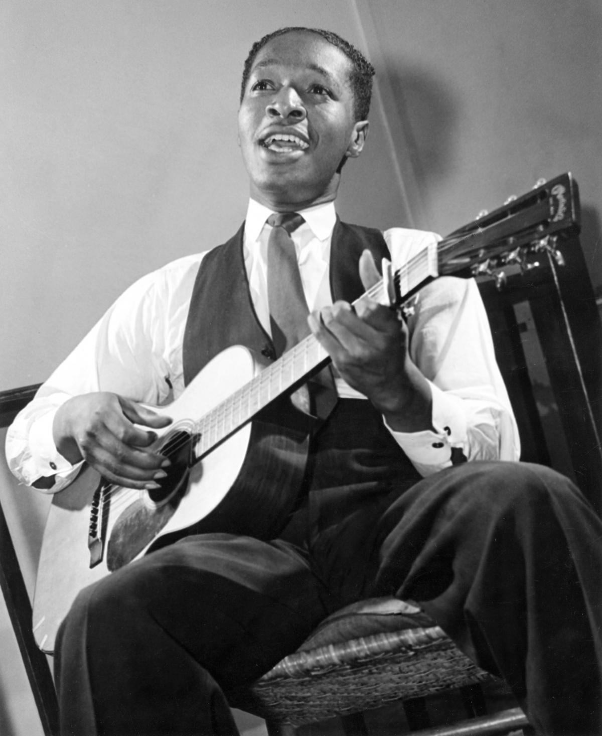 White, wearing a tie and vest, seated, strumming a guitar