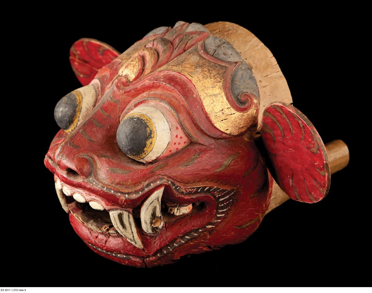 red and gold lion mask, with bulbous eyes and sharp fangs