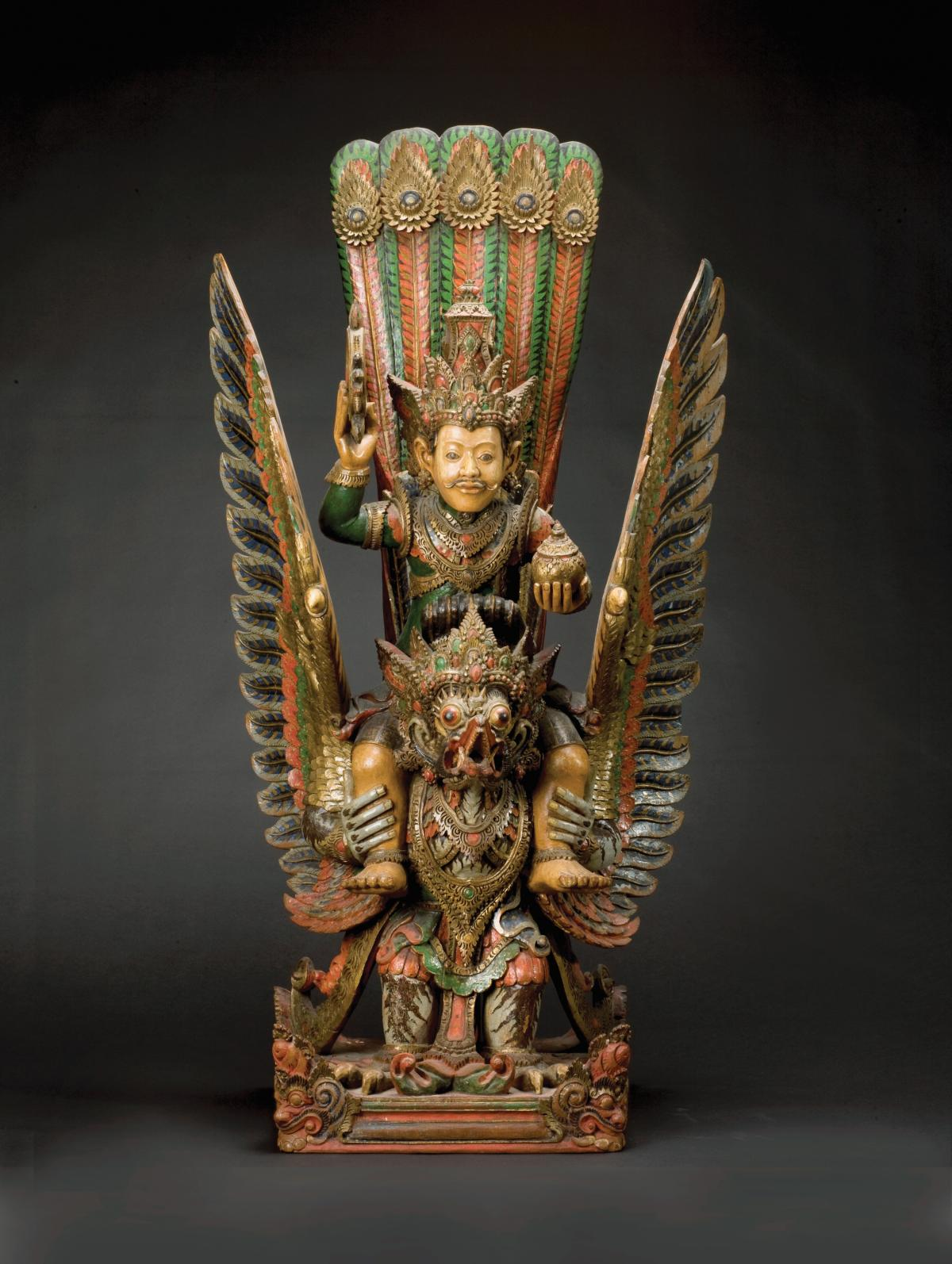 Gold statue of Wisnu, sitting on top of Garuda, painted with aqua, orange and black details