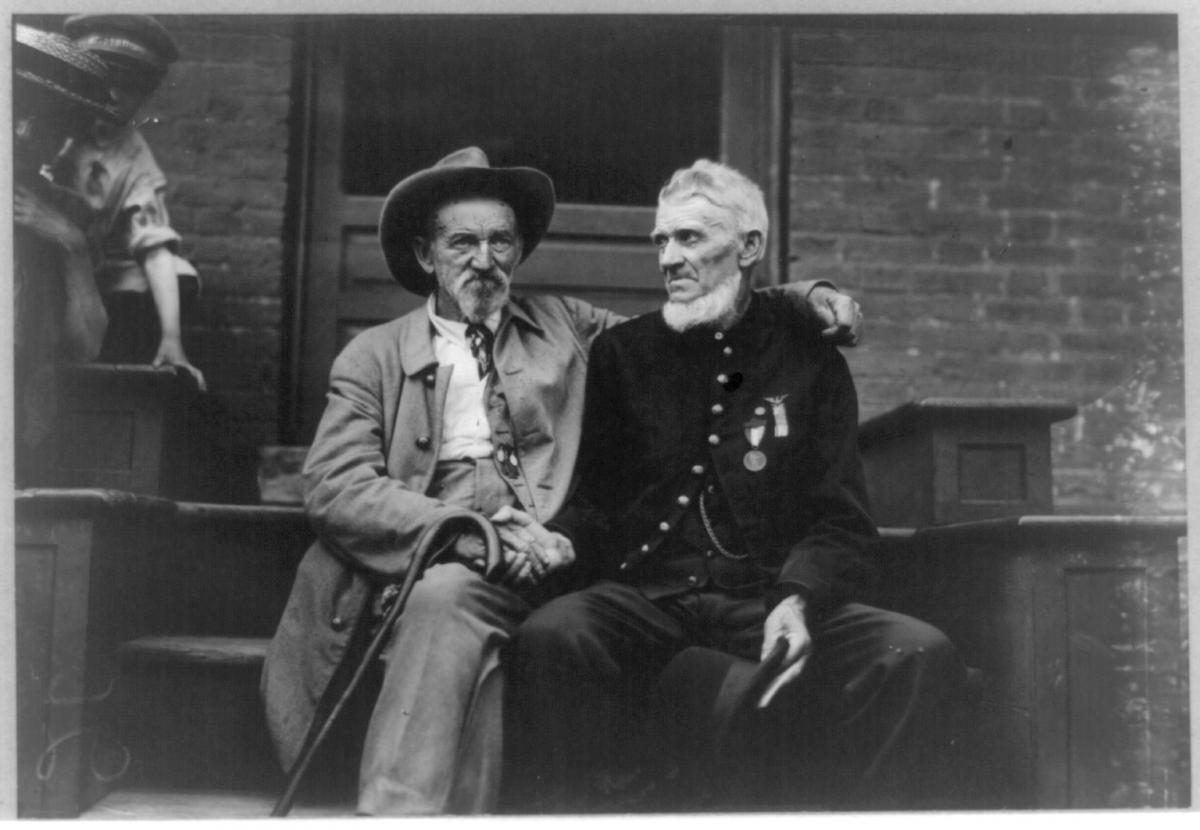 Two elderly men sit on a porch and shake hands