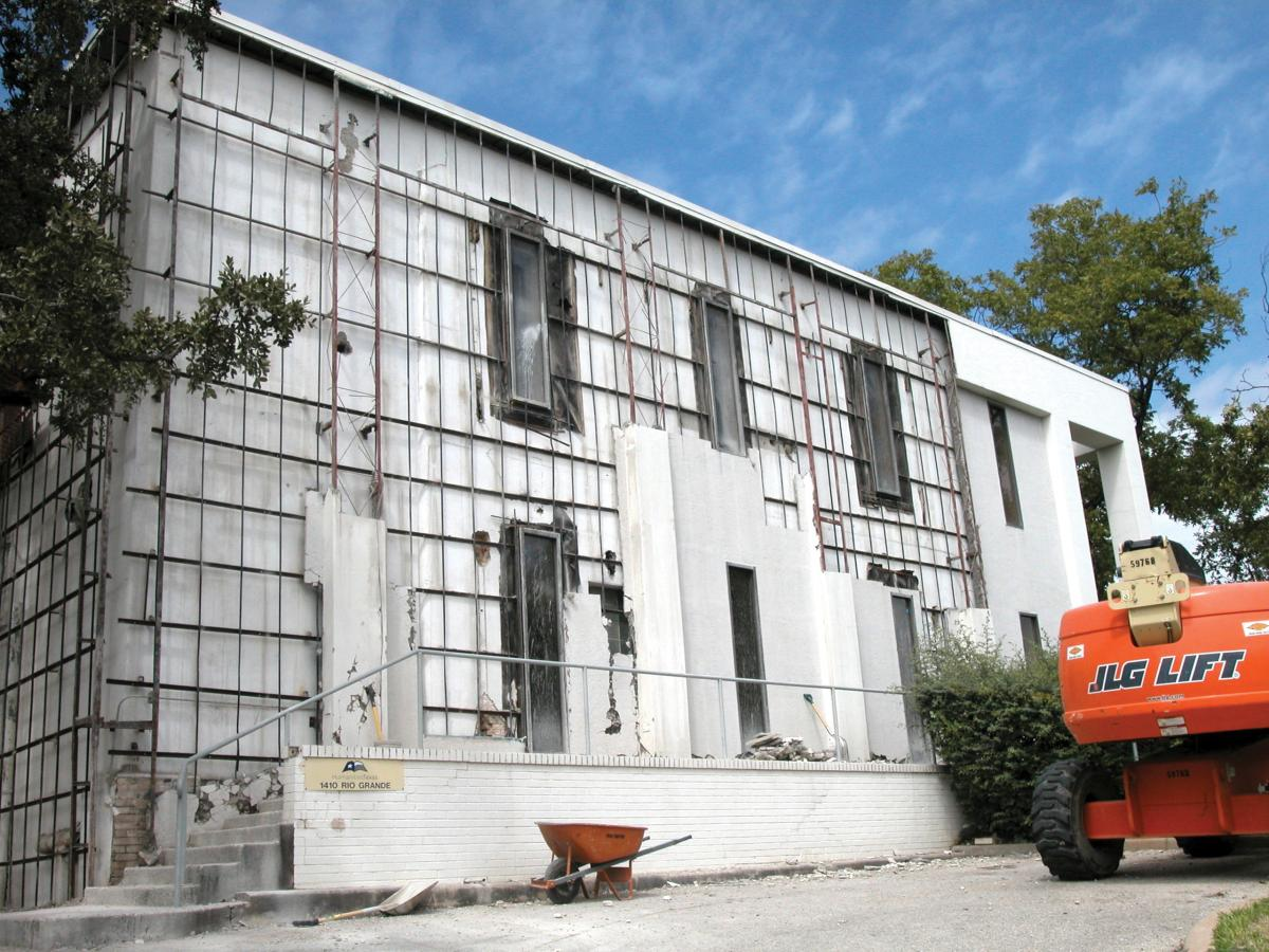 Scaffolding covers the front of the building, while an orange bulldozer sits parked in front