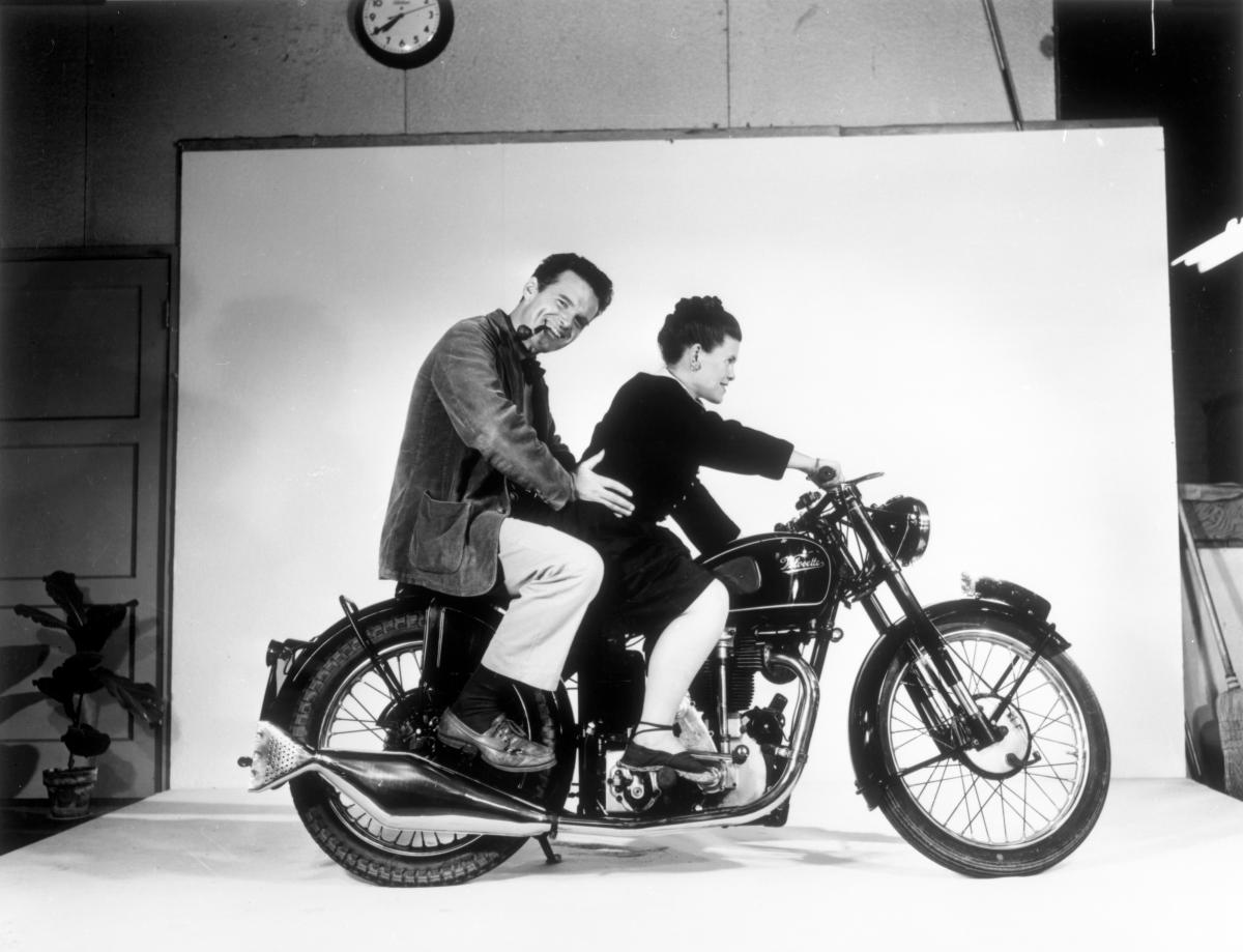 A woman and a man on a motorcycle in front of a film screen, as if they were shooting a picture.