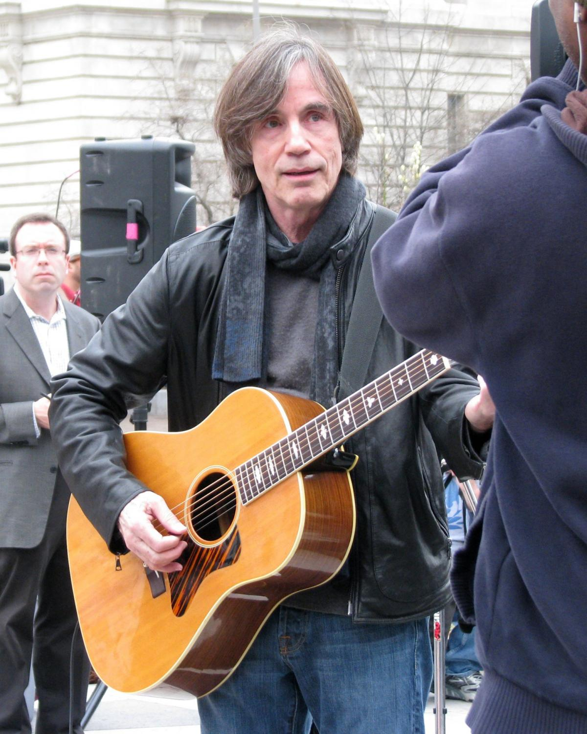 Color photo of a man in a leather jacket playing the guitar.