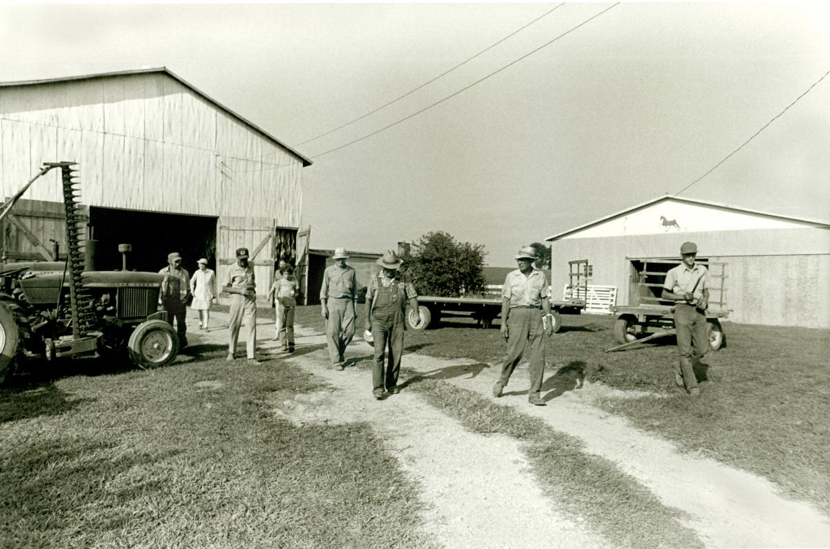 Black and white photo of several men walking out of a barn shed, their harvest tractor nearby.
