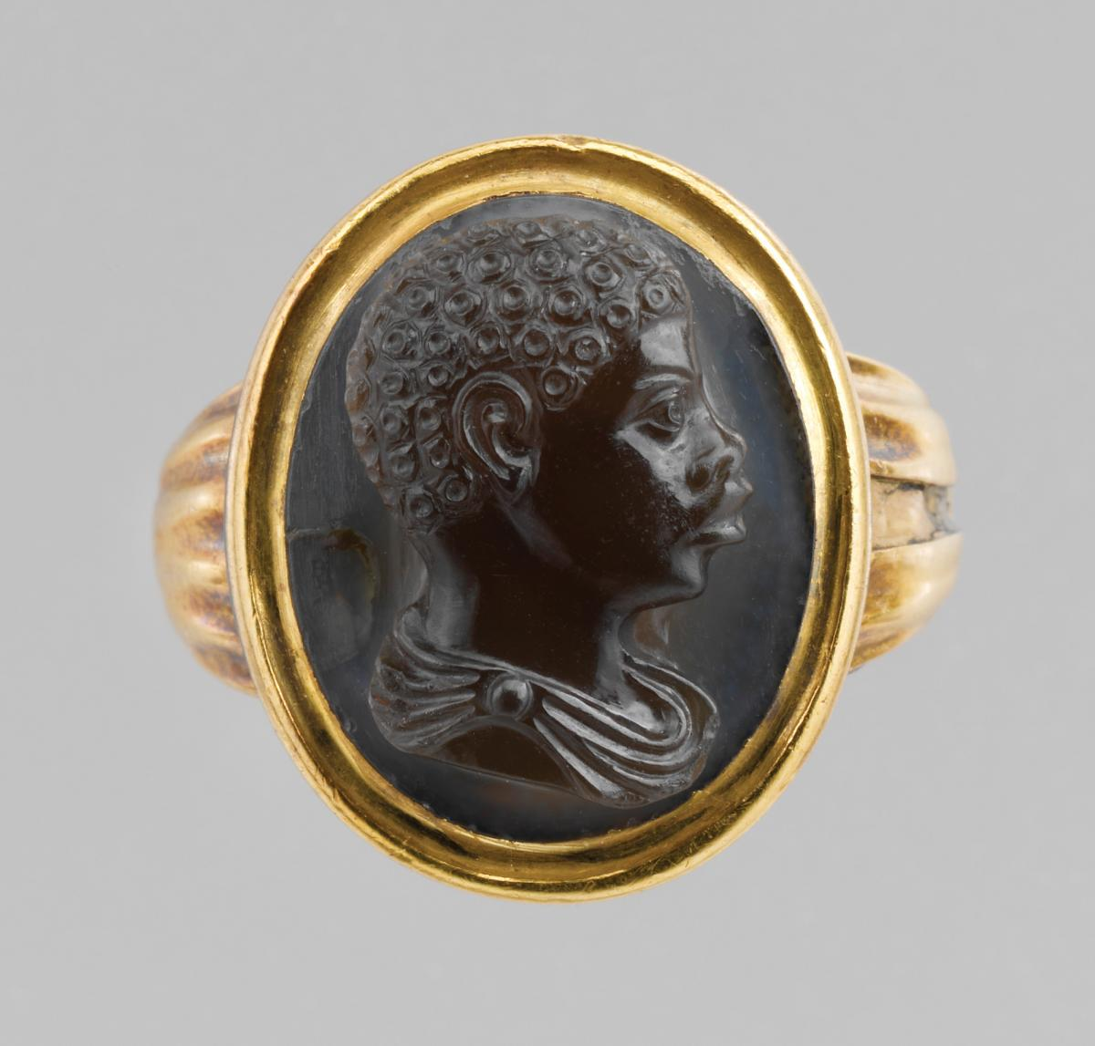 Gold frame with a black stone in the center, carved with the profile of a young African boy