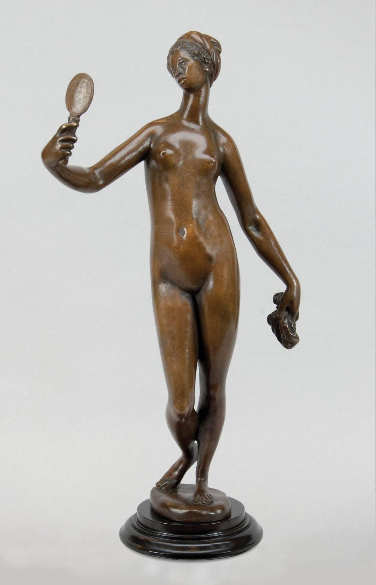 Bronze colored sculpture of a woman looking at herself in a hand-held mirror