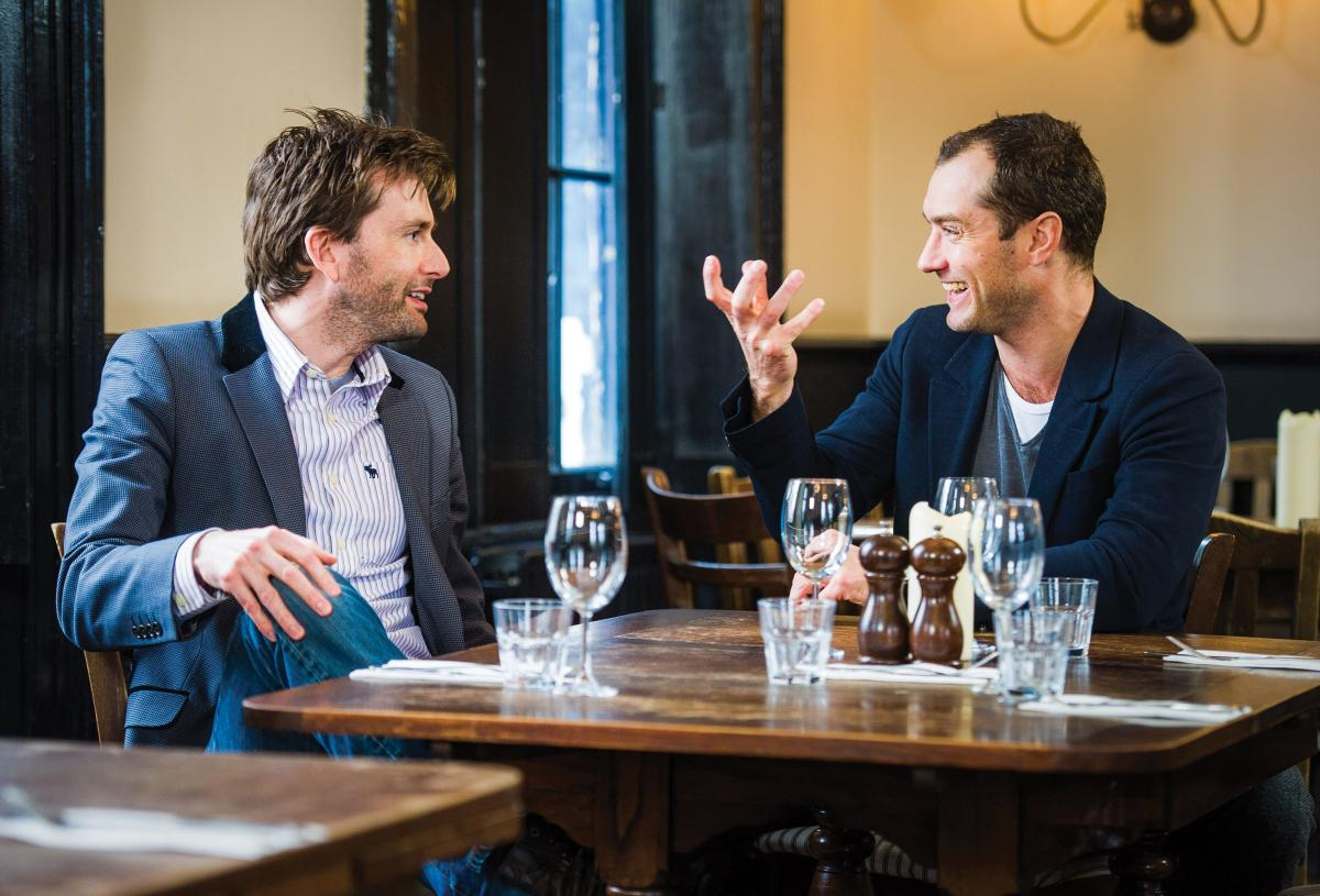 Tennant and Law sit at a table, set with water glasses, laughing and talking