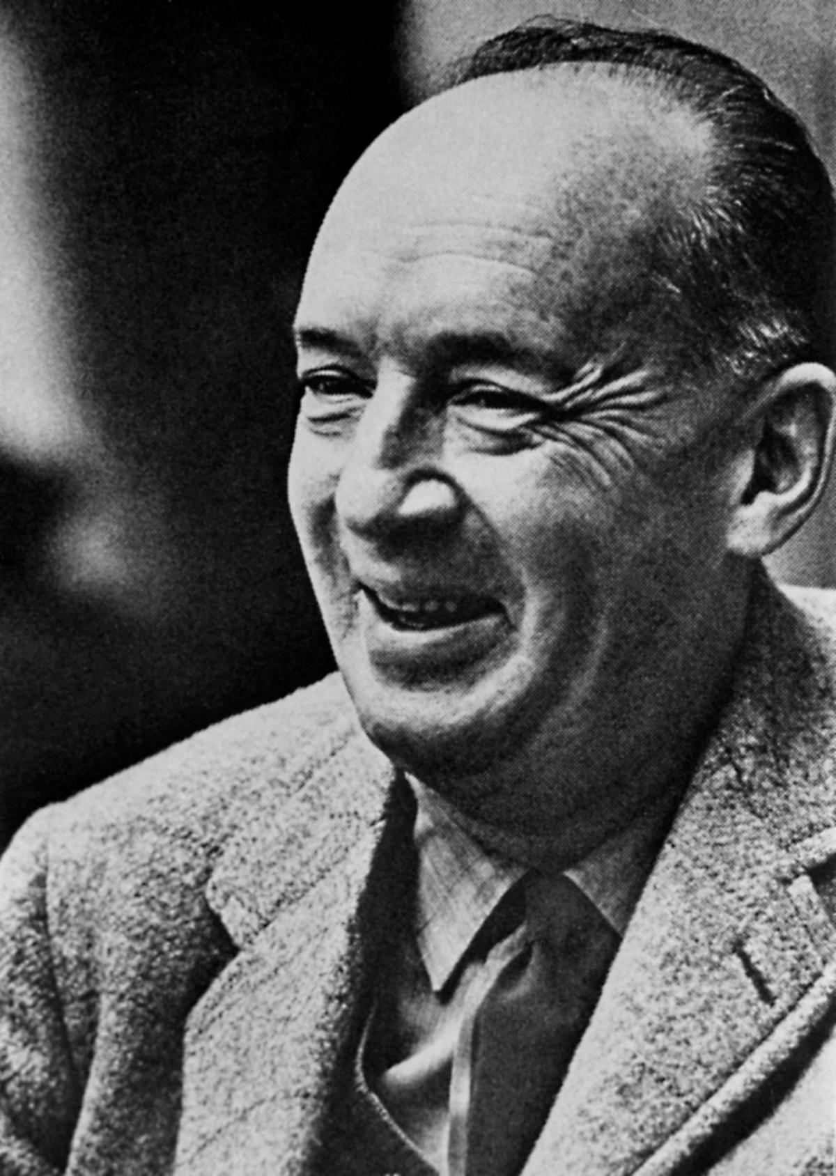 Head and shoulders photo of Nabokov, clean shaven and in a grey suit, striped tie