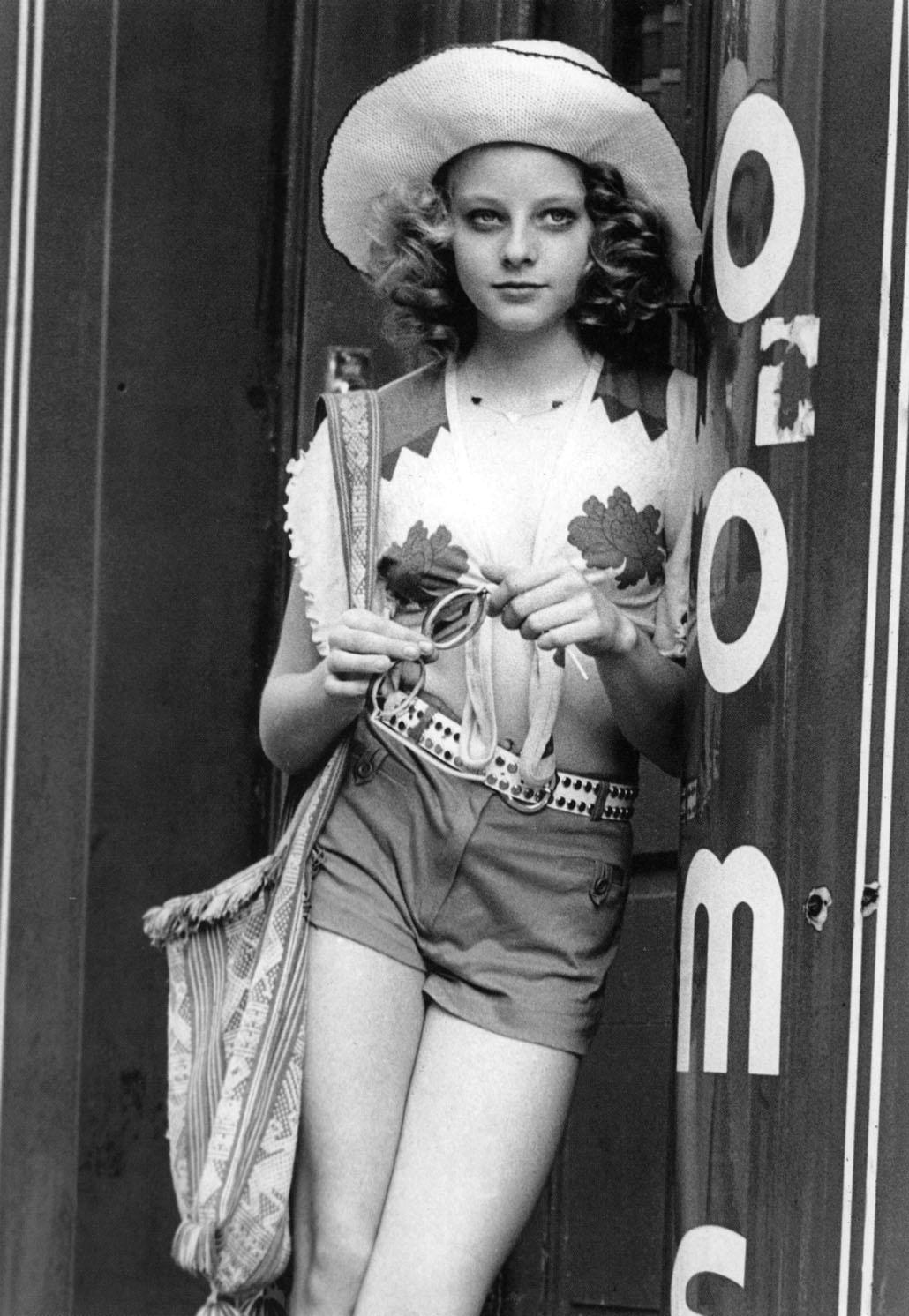 Foster, in a wide brimmed straw hat, shorts, and a string-tied blouse, leaning in a doorway