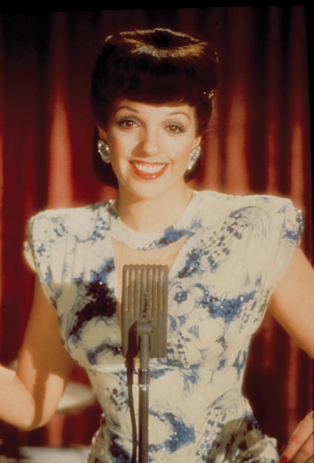 Minnelli with a beehive hairdo, wearing a blue, flowered dress, in front of a microphone, red curtain in the background
