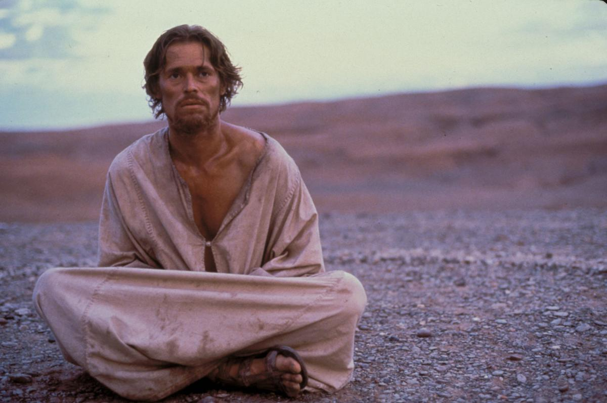 Dafoe, sitting on barren ground, wrapped in dirty rags