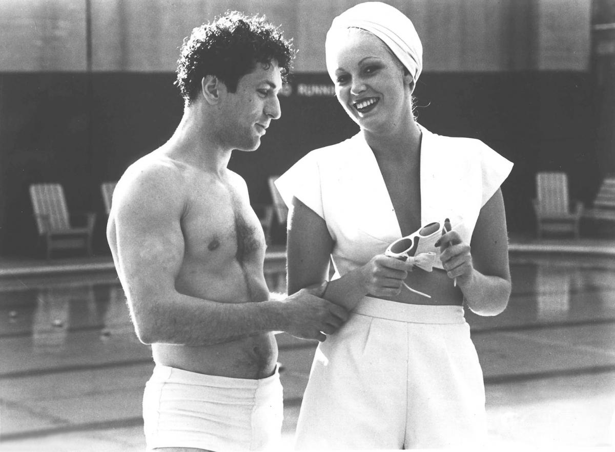 Shirtless Jake and Vicki, wearing a white swimsuit and bathing cap, talk, in this still from Raging Bull