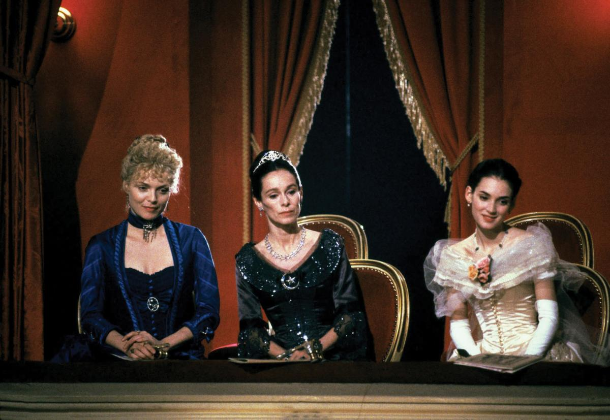 The three actresses, sitting in a velvet draped opera box, wearing elaborate velvet and chiffon dresses