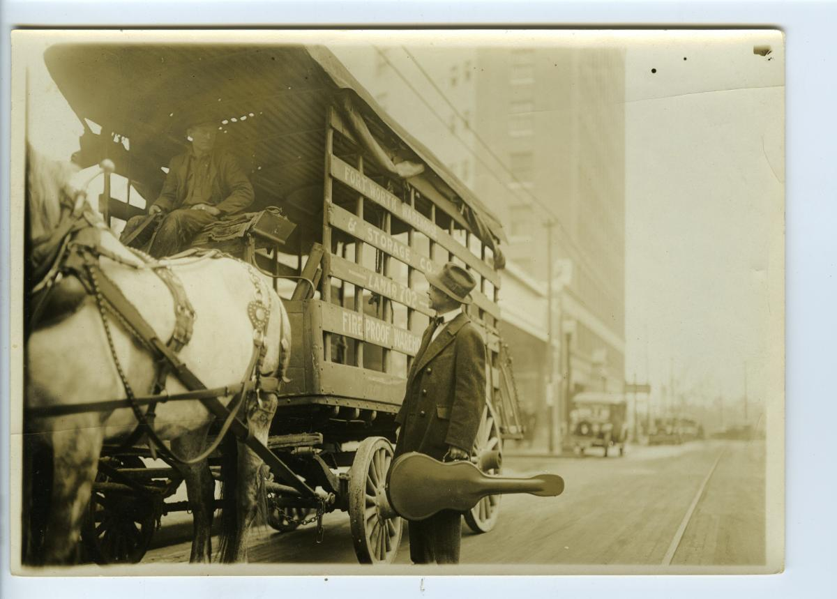 Sandburg, with guitar case in hand, stops to talk to a man driving a horse-drawn wagon, on the street