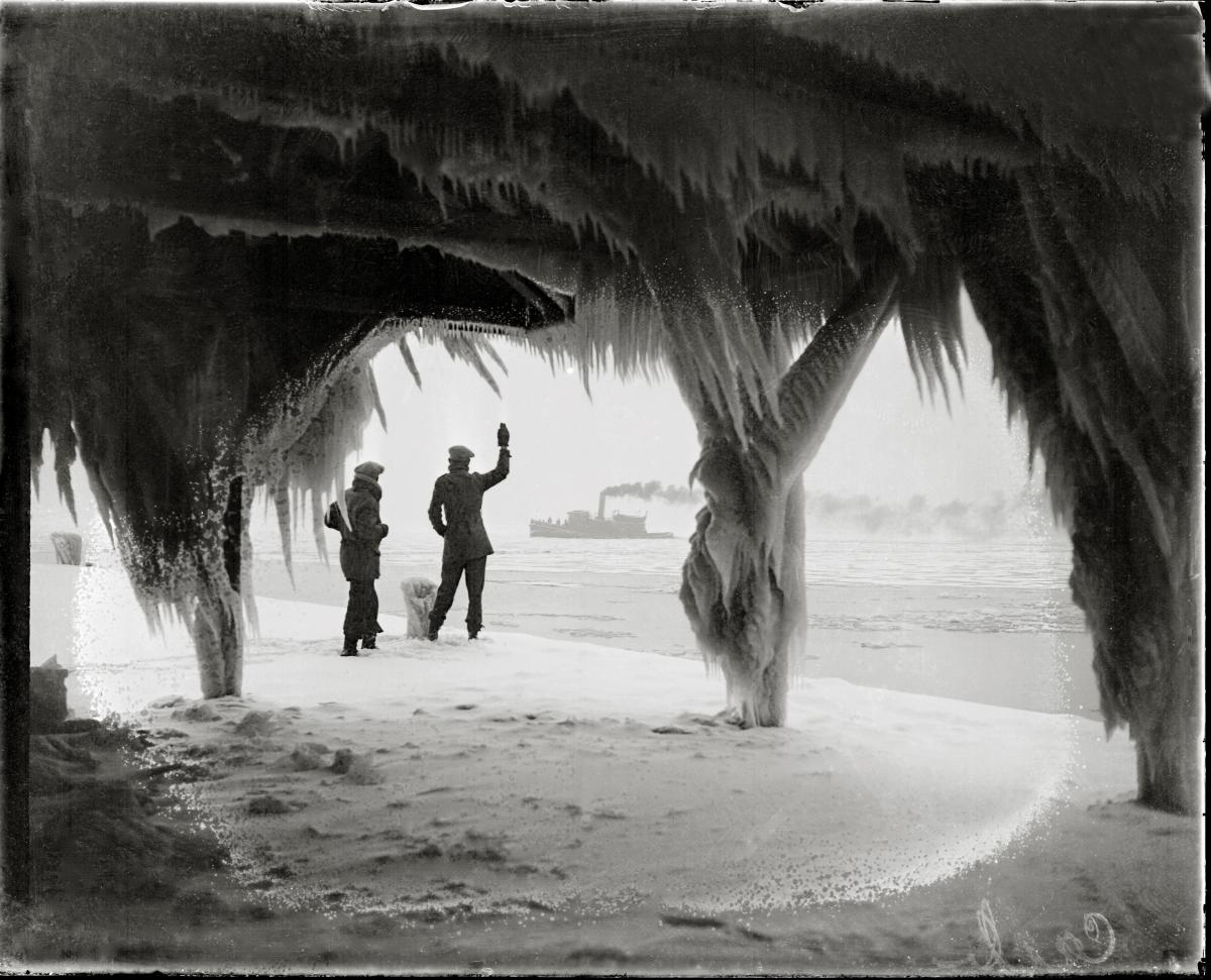 Two men examine the ice buildup, which has formed long icicles