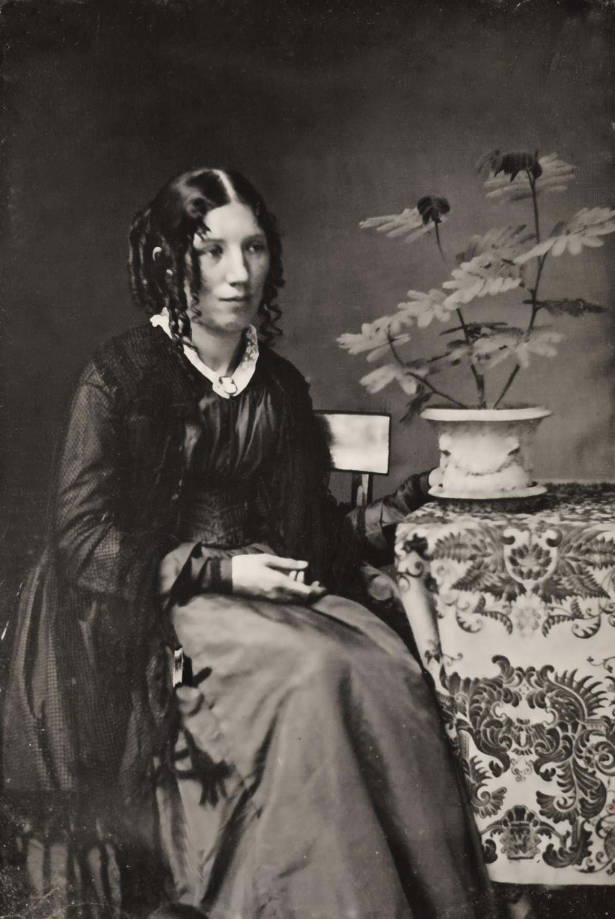 Stowe, with curled hair and wearing a dark shawl and dress, seated next to a table with a flower in a vase