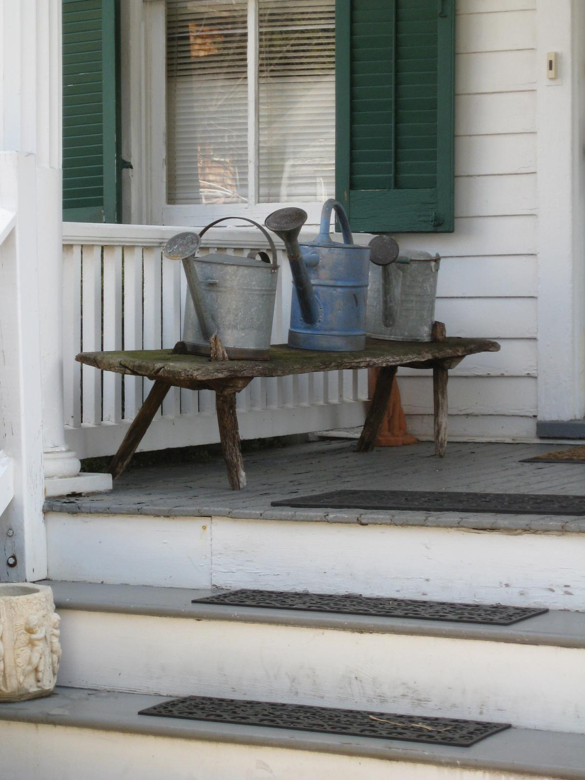 Photograph of front porch, bench with metal buckets on it