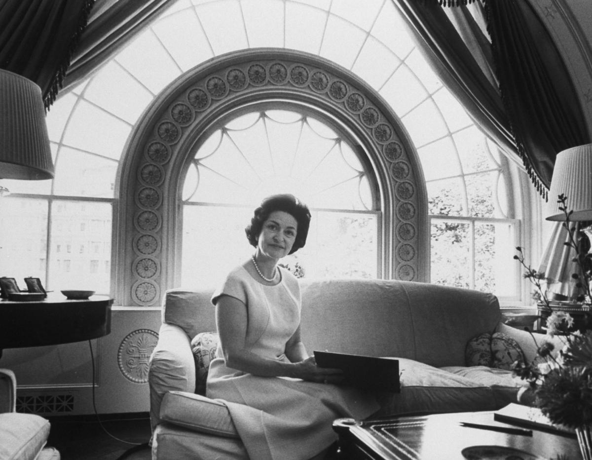 Black and white photograph of Lady Bird Johnson sitting on couch in White House