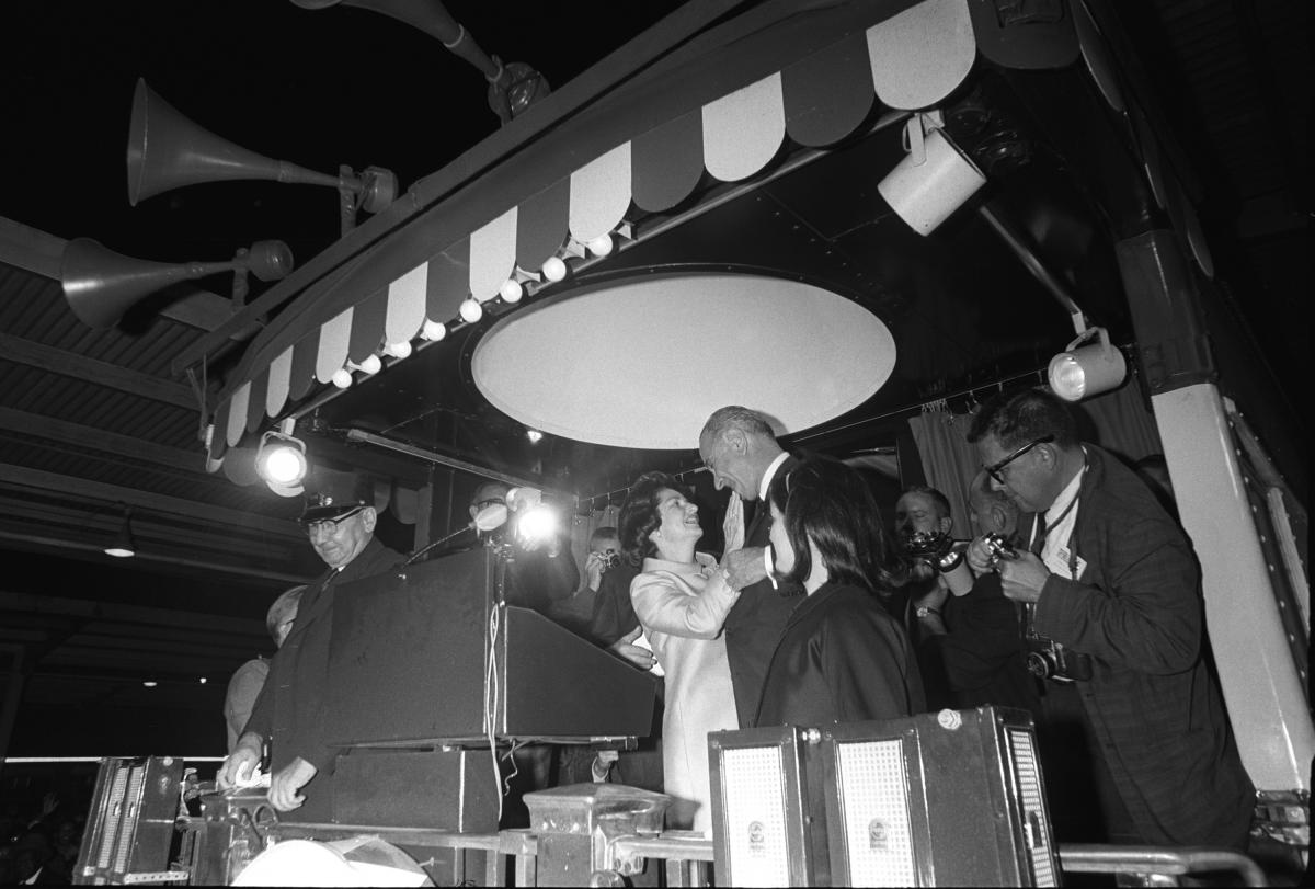 Black and white photo of Lady Bird Johnson embracing her husband behind a podium