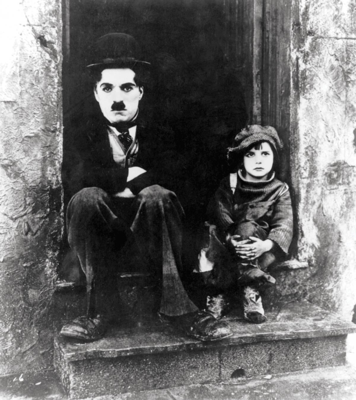 Black and white still of Charlie Chaplin and Jackie Coogan sitting on stoop