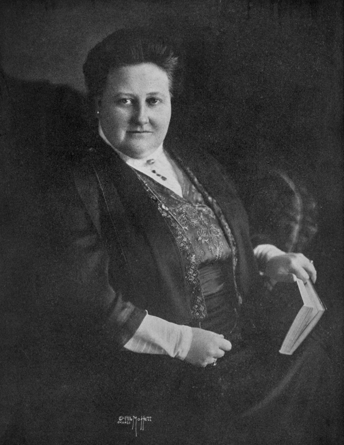 Lowell, wearing a black dress with a high necked white collar, seated