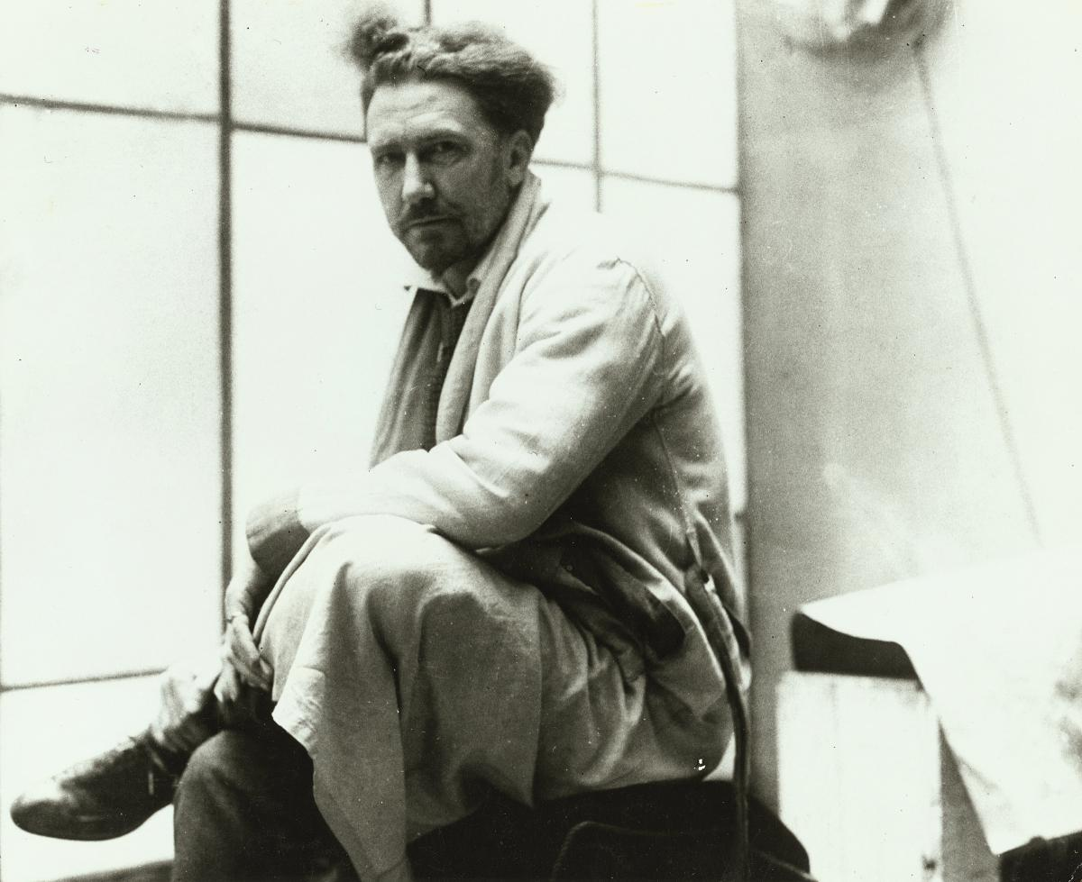 black and white photo of one of Ezra Pound, sitting with his legs crossed