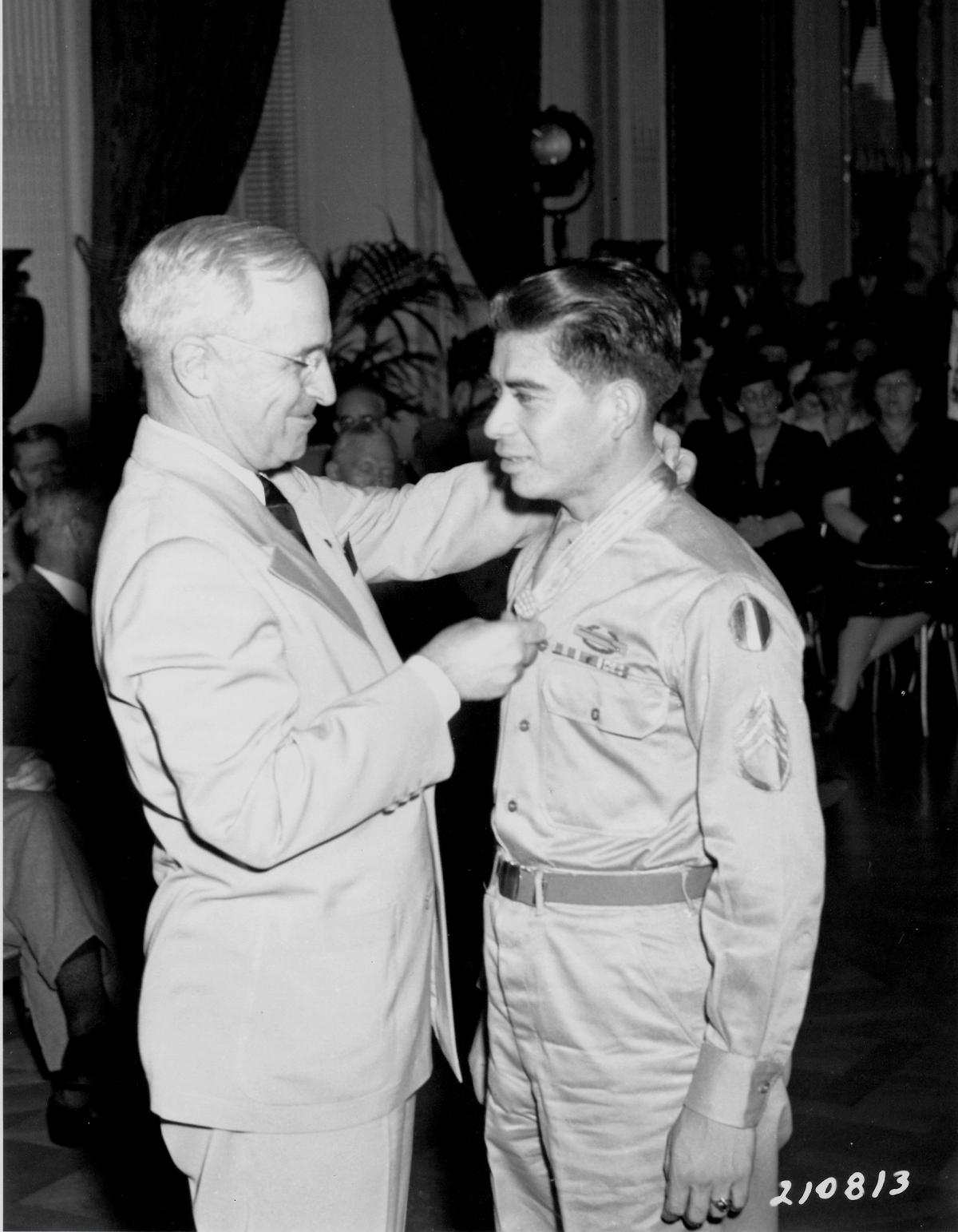 President Truman places the medal around Garcia's neck