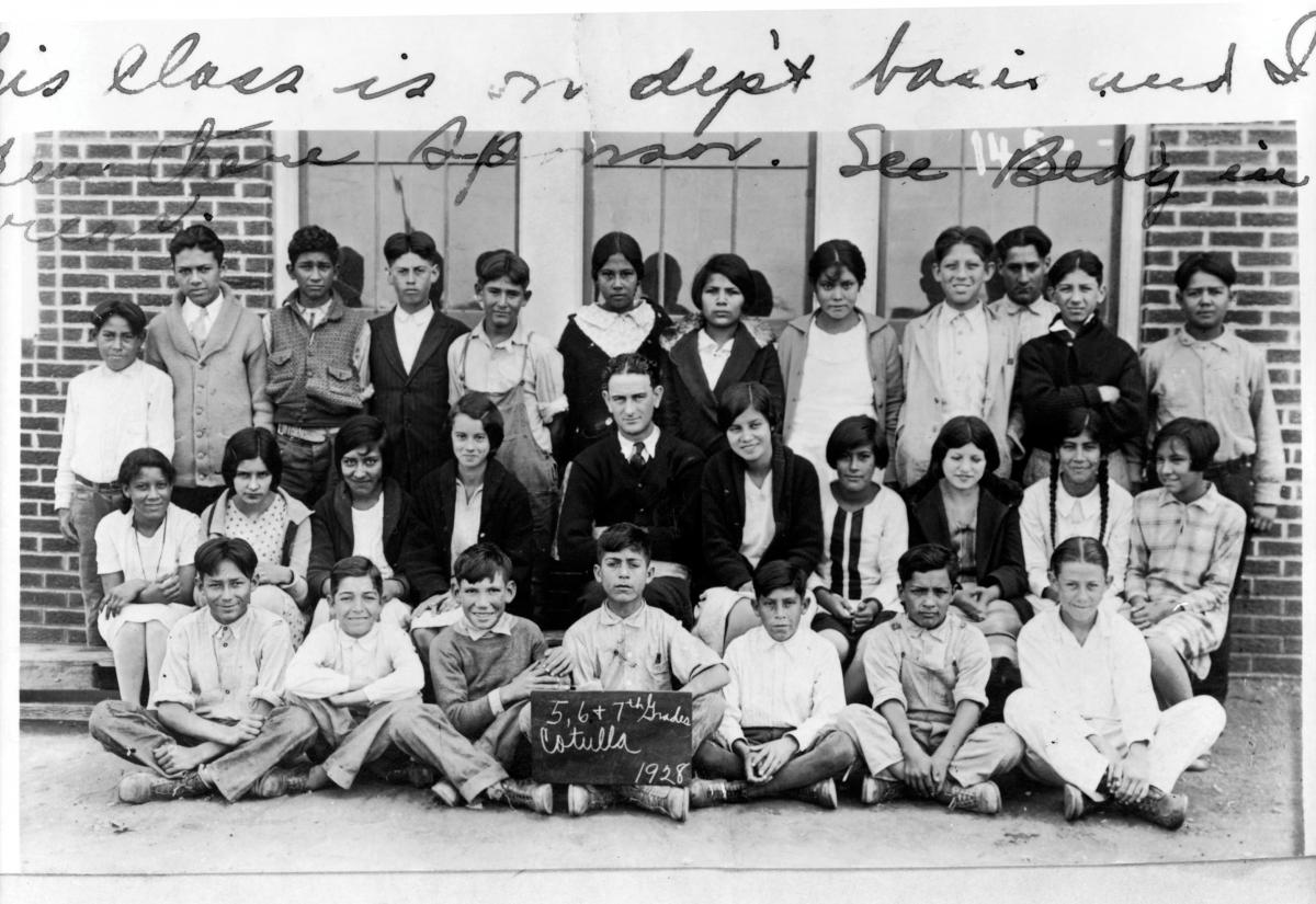 Young Lyndon Johnson, sitting amongst Mexican-American schoolchildren in front of a school building