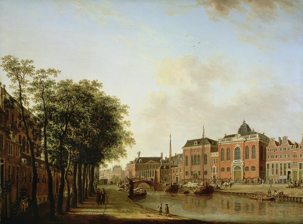 View of red brick buildings overlooking a canal, with a stand of trees on the left hand bank