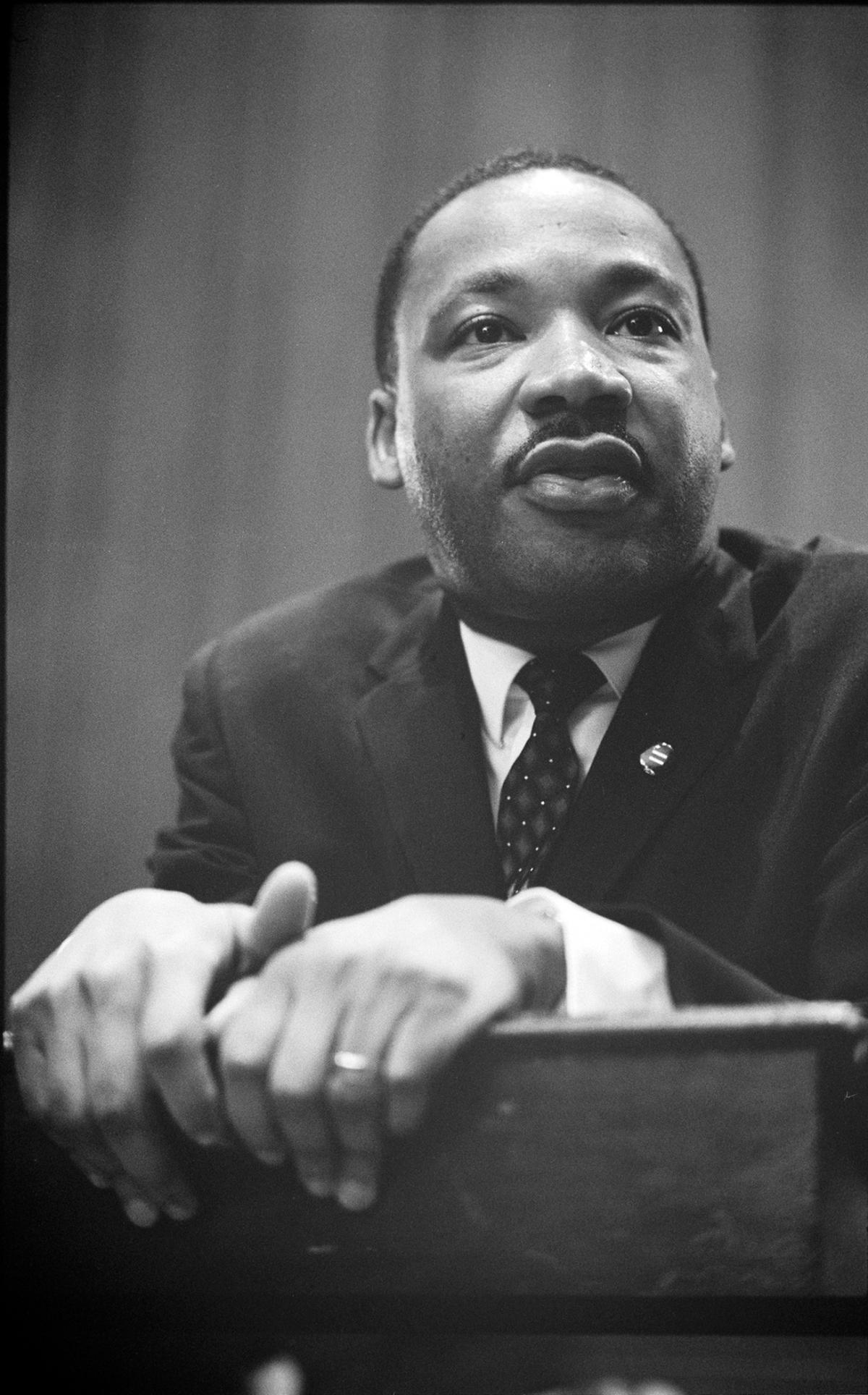 Black and white picture of Martin Luther King Jr. leaning on a podium
