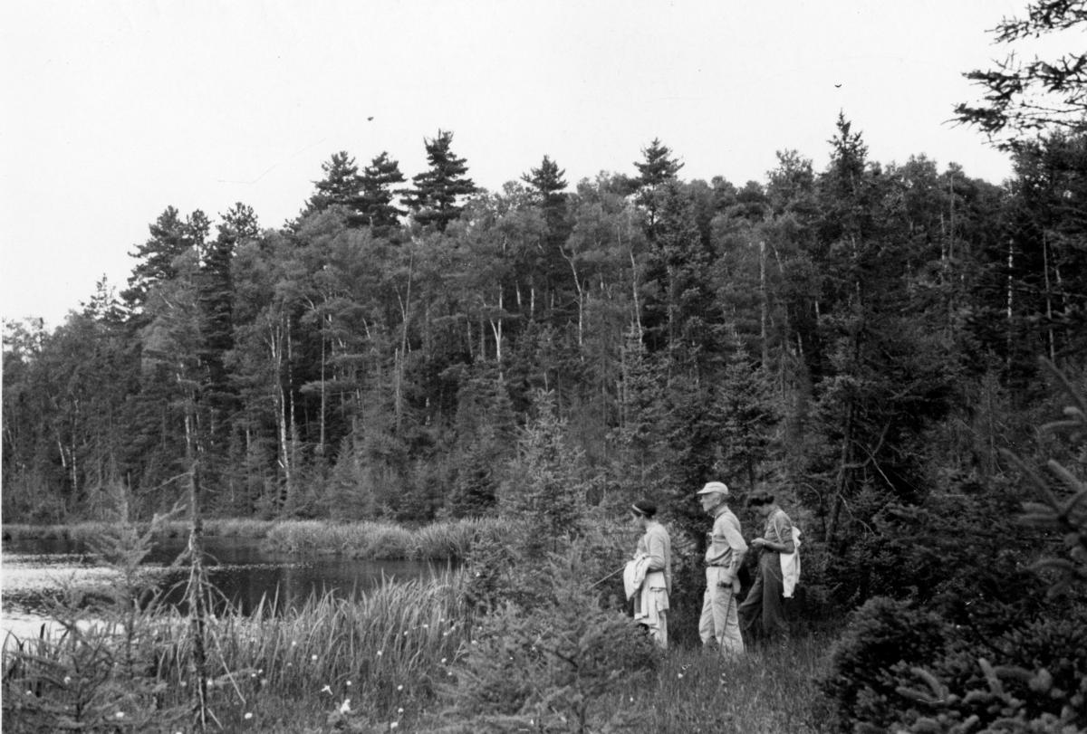 Black and white landscape photo with three people in foreground