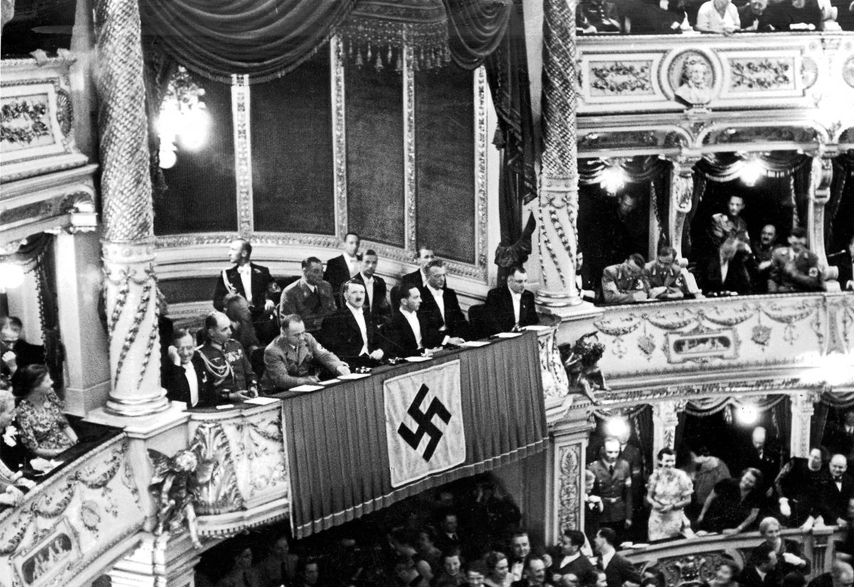 Black and white photo of the theatre box, hung with a nazi flag, in which Hitler sits with his party leaders at the Austrian opera