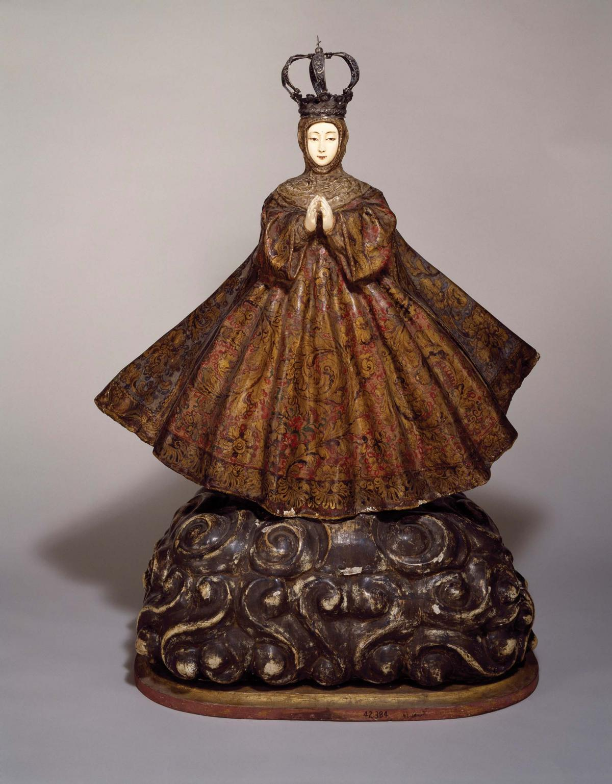 ivory statue of Mary, wearing a wide, brown, embroidered skirt and crown