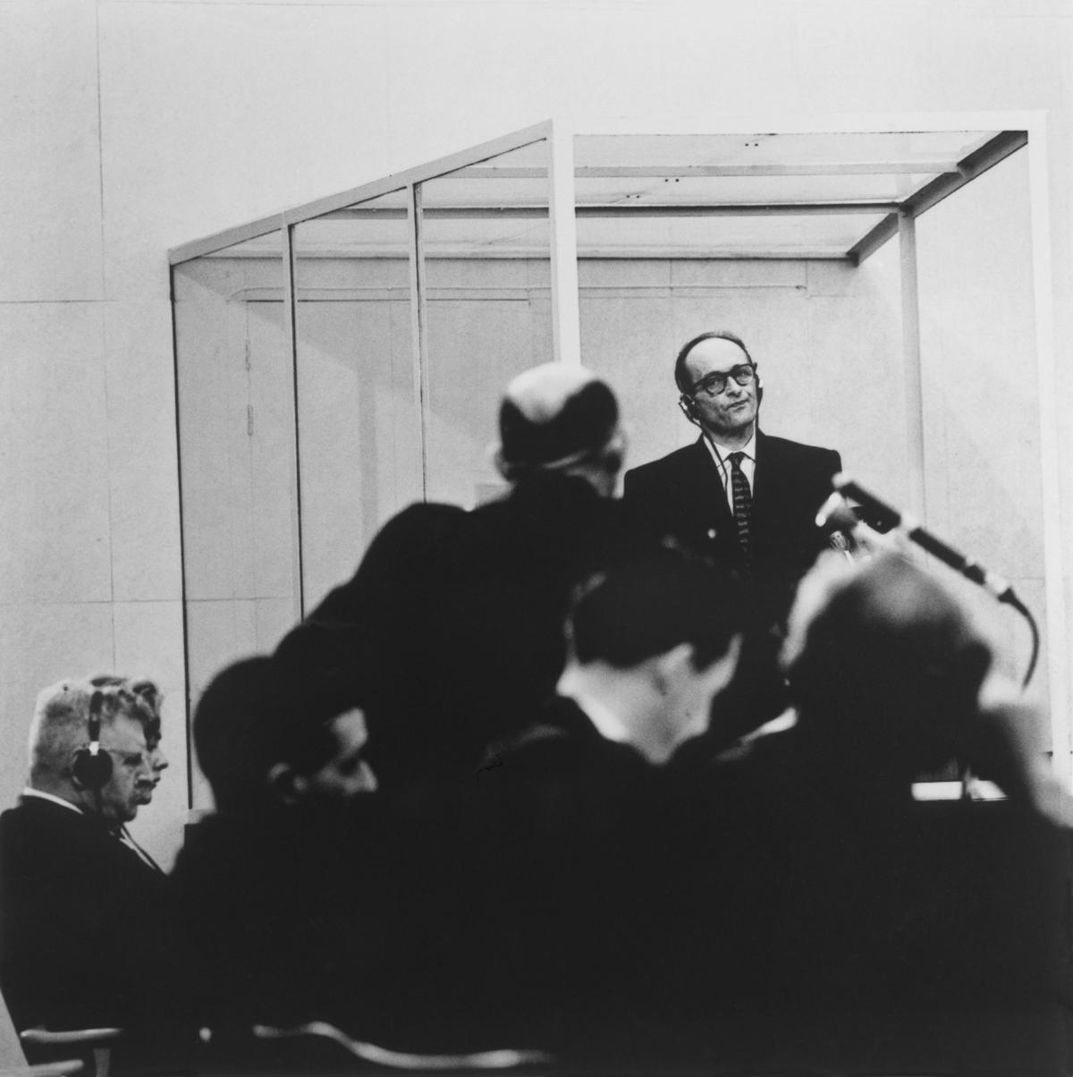 Eichmann, wearing glasses, a dark suit, and headphones, purses his lips at a lawyer in the foreground, who is questioning him, hands on his hips