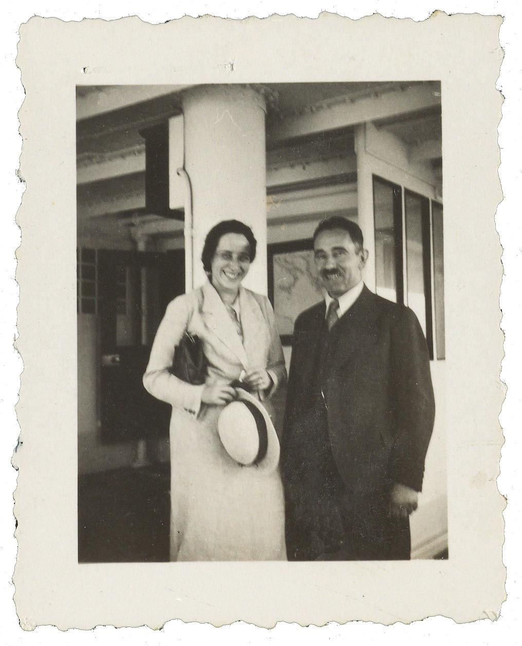 Arendt, smiling and wearing a long white coat, holding a hat, stands next to a moustached man in a dark suit