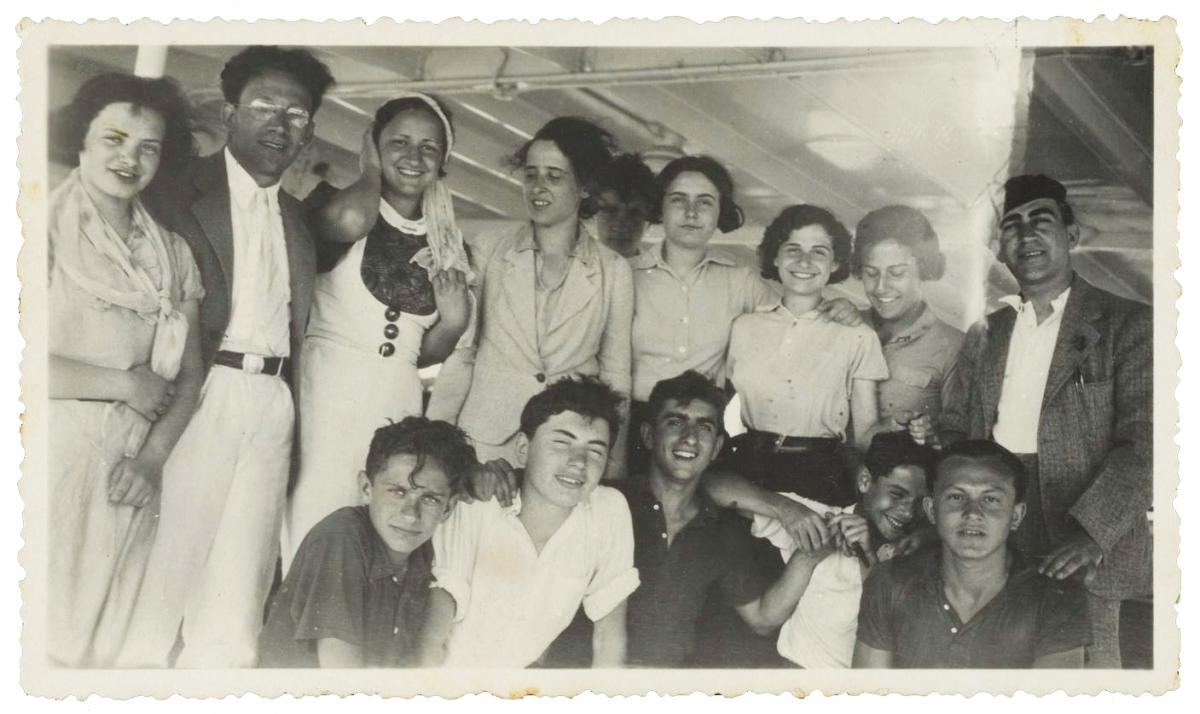 A group of young men and women pose, kneeling and standing in two rows, smiling, with their arms around each other