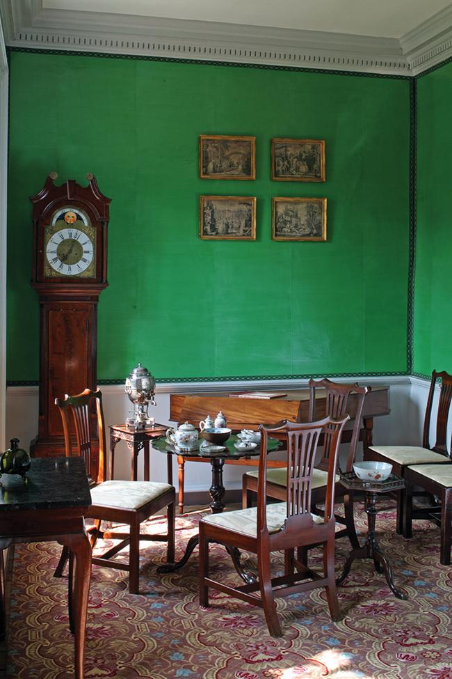 Green walls with crown molding, dark wood grandfather clock in the corner, and several wooden chairs, a coffee table and a desk