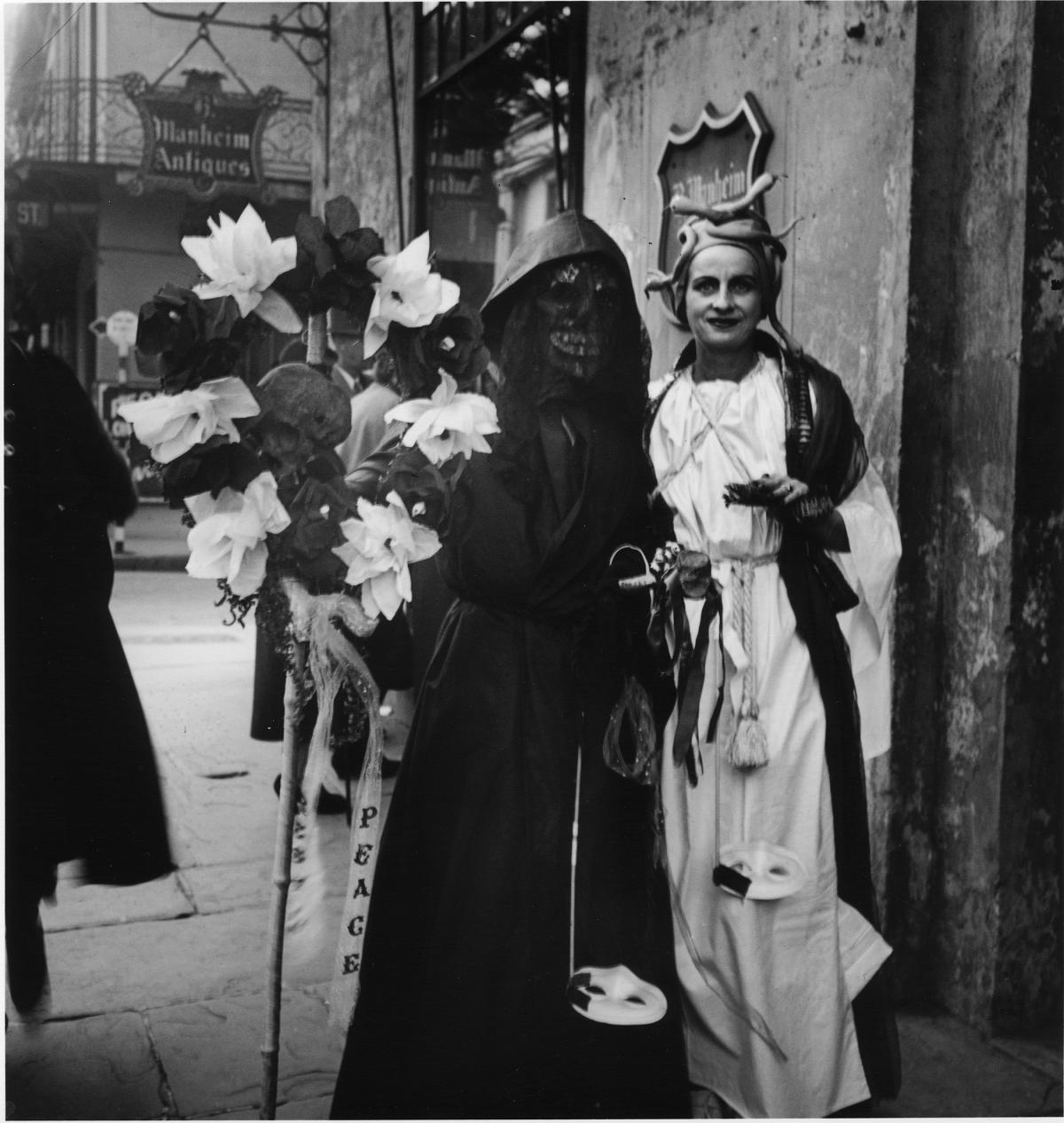 Two revelers stand on a New Orleans street; one wearing a long white robe and snake-topped cap, the other in a hooded black robe, black skull mask, and holding a wreath of black and white flowers