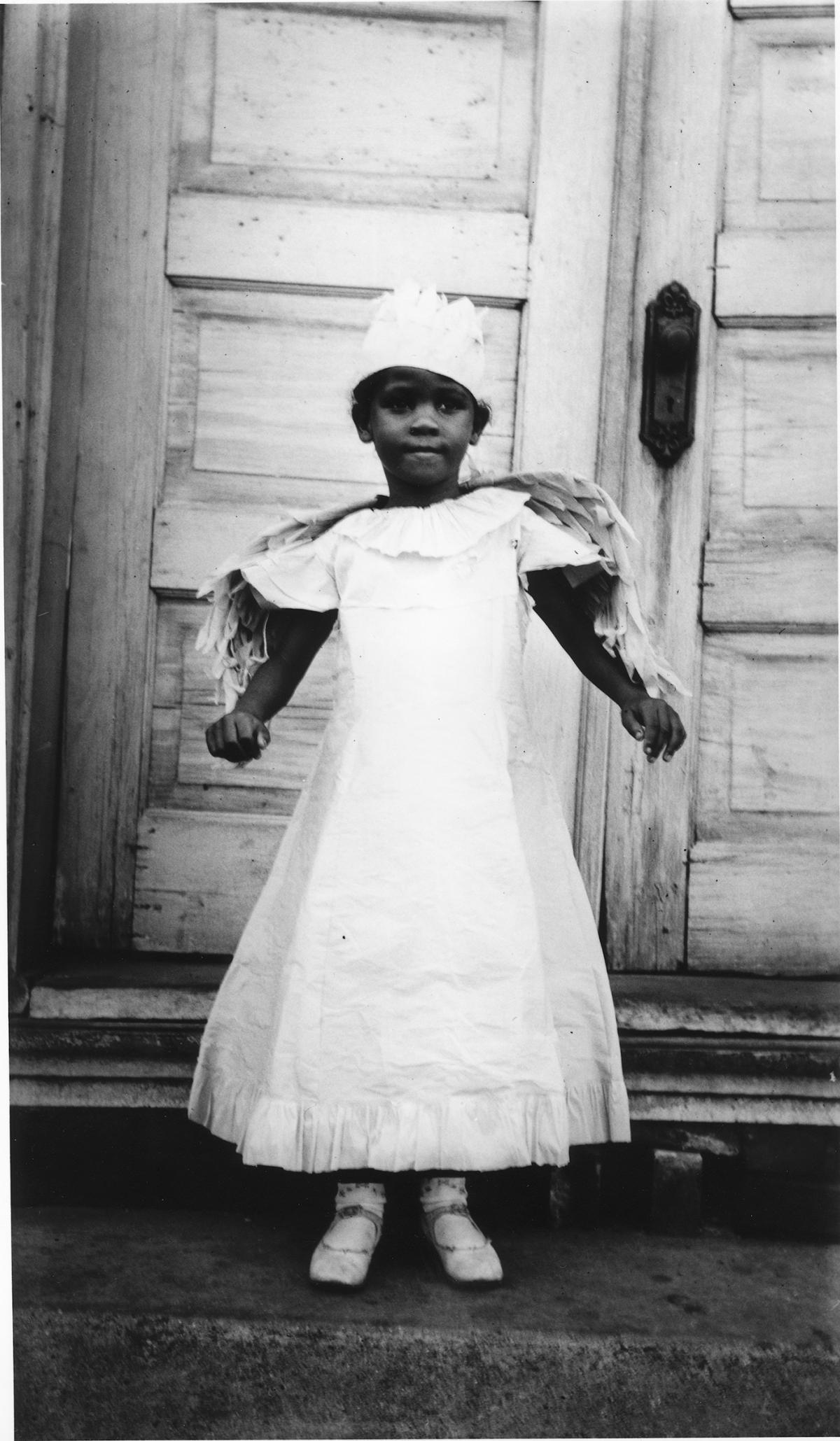 A young African American girl wears a white dress with wings sewn into the shoulders and a feathered flat cap