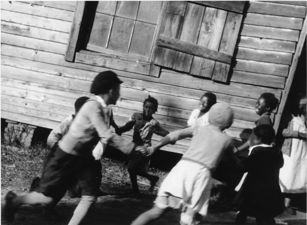 A group of schoolchildren link arms and run around in a circle in front of a wooden building