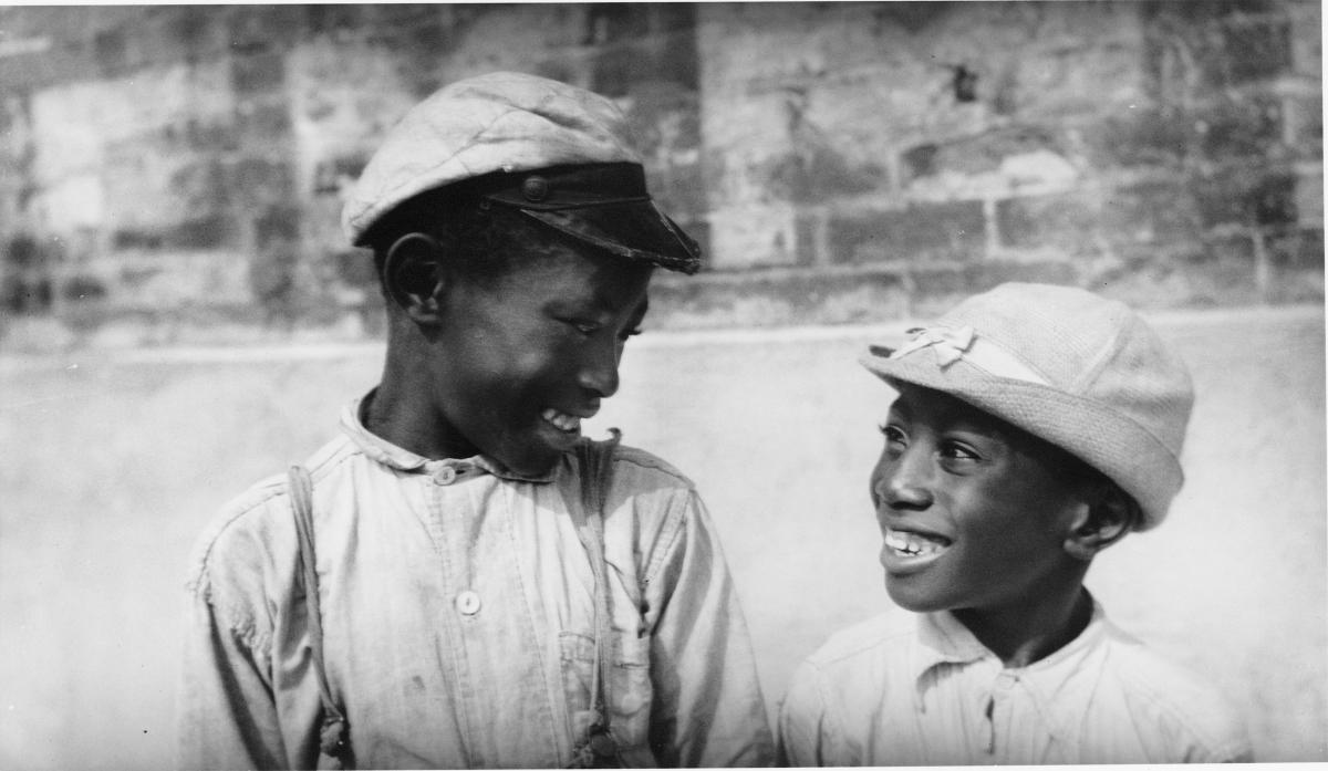 a pair of African American boys, both wearing caps, smile and look at each other