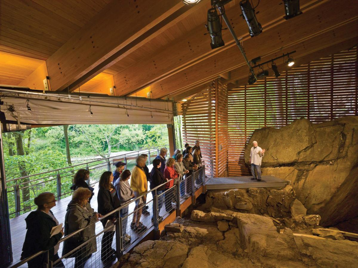 Visitors line up at a railing as Adovasio gestures to the rocky excavation site