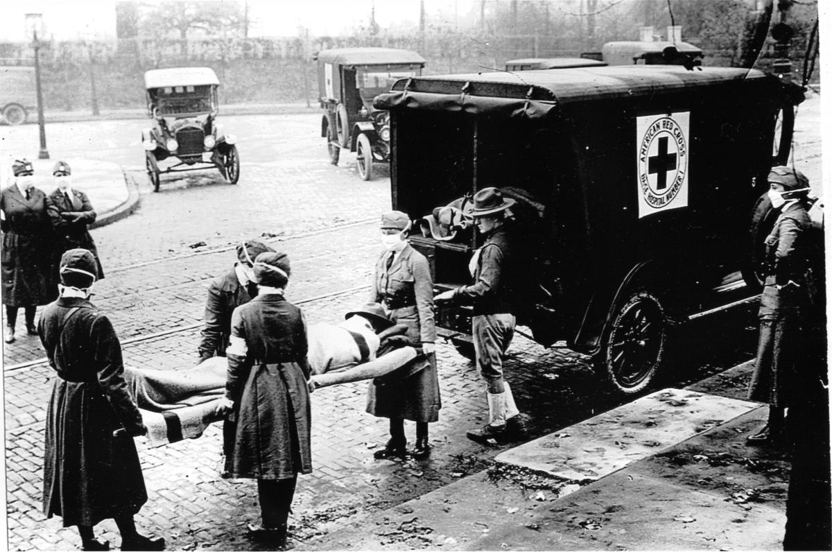 Four masked volunteers carry a covered body on a gurney into a Red Cross truck, while masked officials look on from the sidewalk