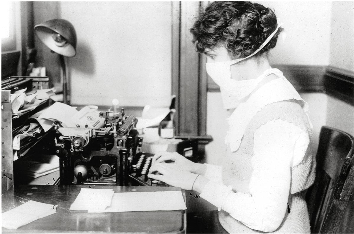 A woman types on a typewriter while wearing a thick white flu mask