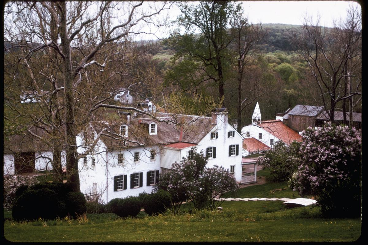 A view of Hopewell Furnace from a hill: white houses with brown roofs and chimneys, with a church to the far right