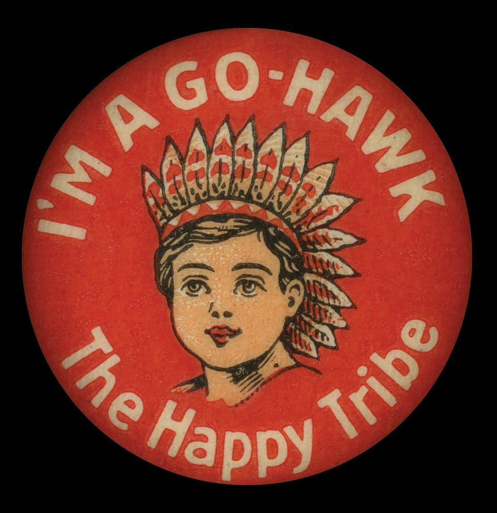 "Image of a ""Go-Hawk"" pin in red, with an illustration of an Indian women in the center and the words, ""The Happy Tribe"" underneath her."