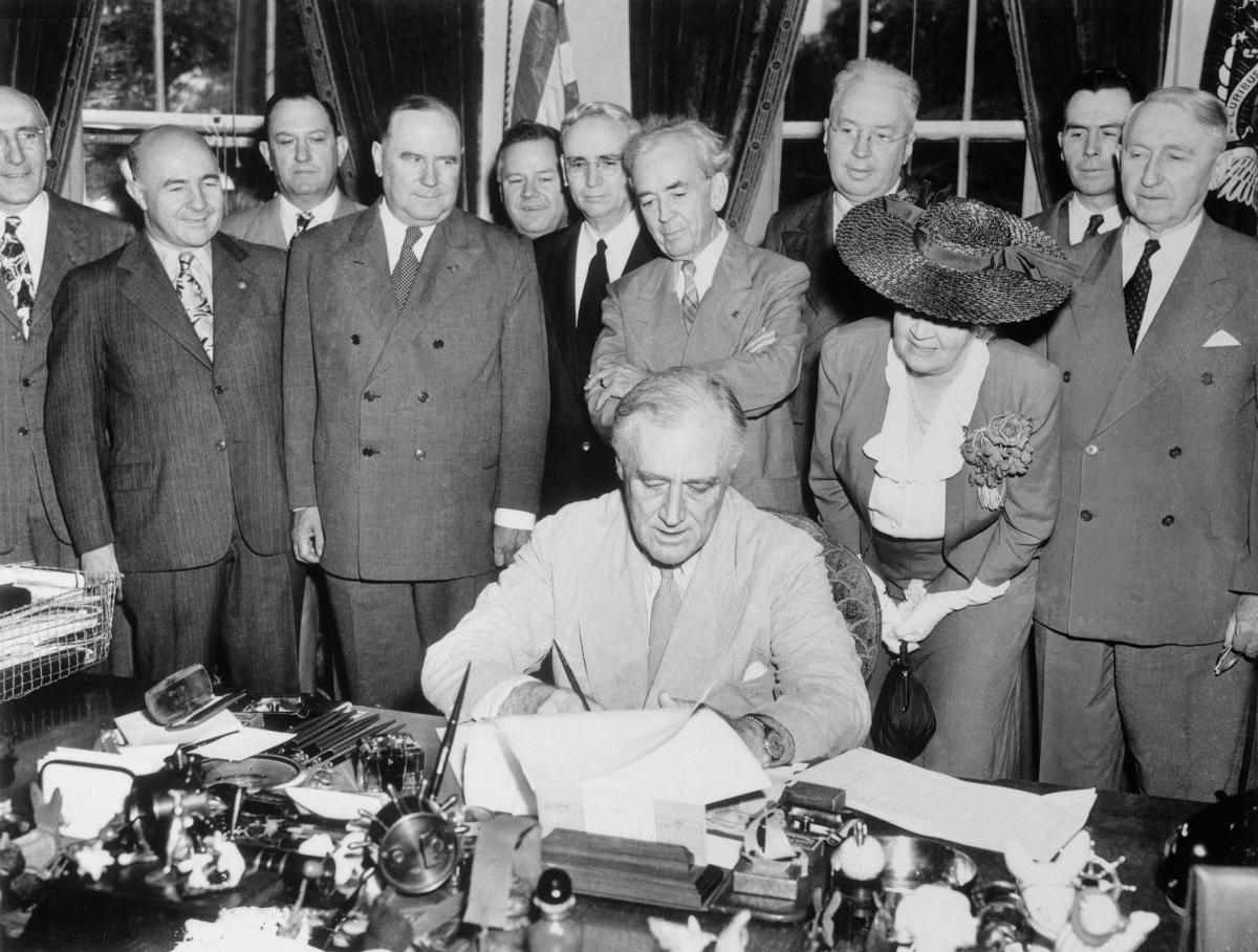 FDR, with his advisors standing behind him, signs the G.I Bill at his desk in the oval office