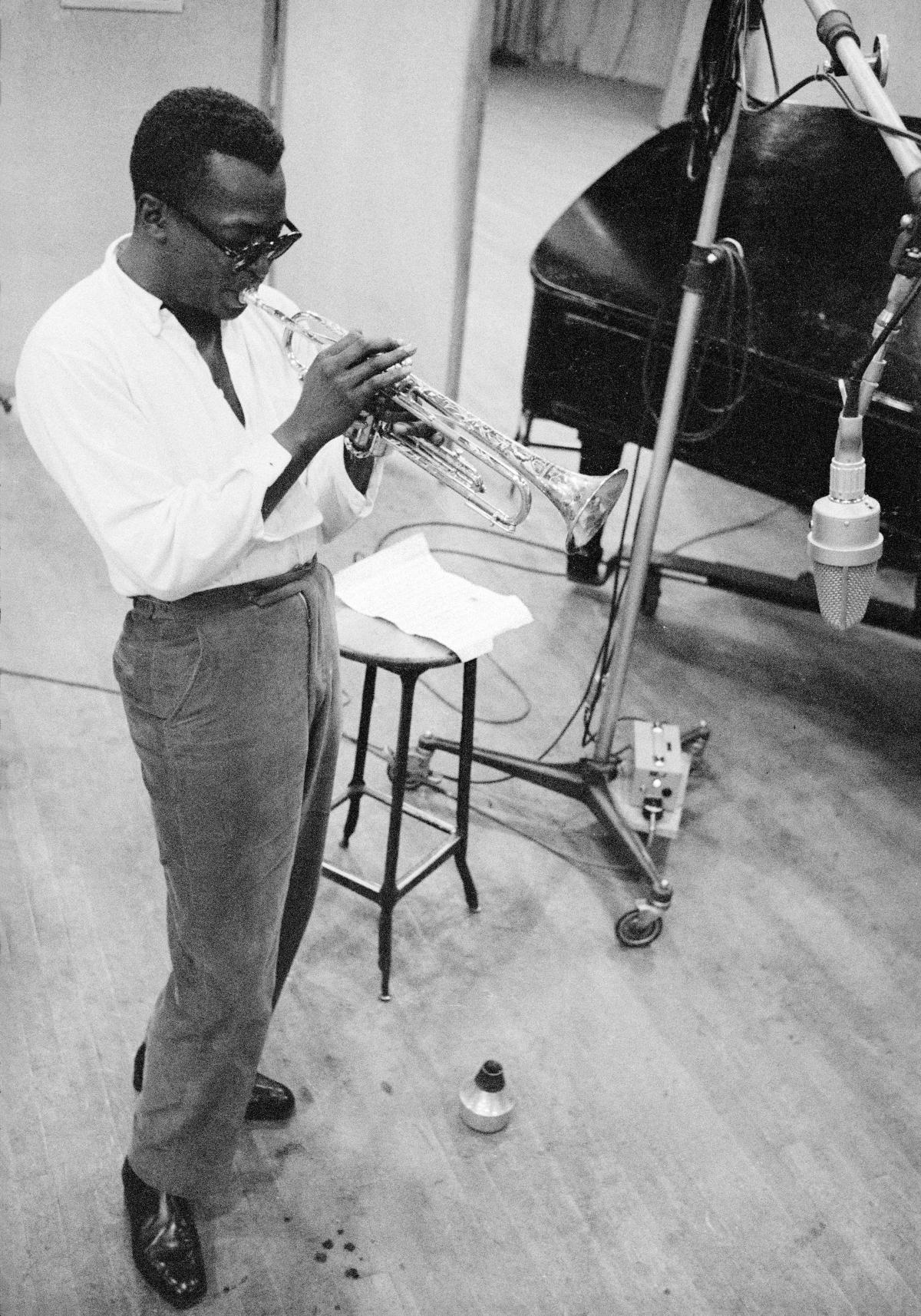 Davis, playing a trombone, wearing dark glasses